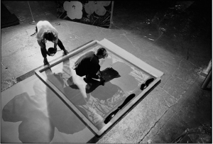Andy Warhol and Gerard Malanga silkscreening the background onto a Flowers painting.